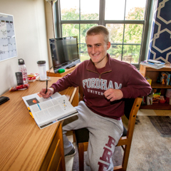 Male Student at Desk in Dorm Room