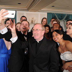 Father McShane takes selfie with students at Founder's Gala