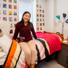 Female student sitting on bed in dorm room - SM