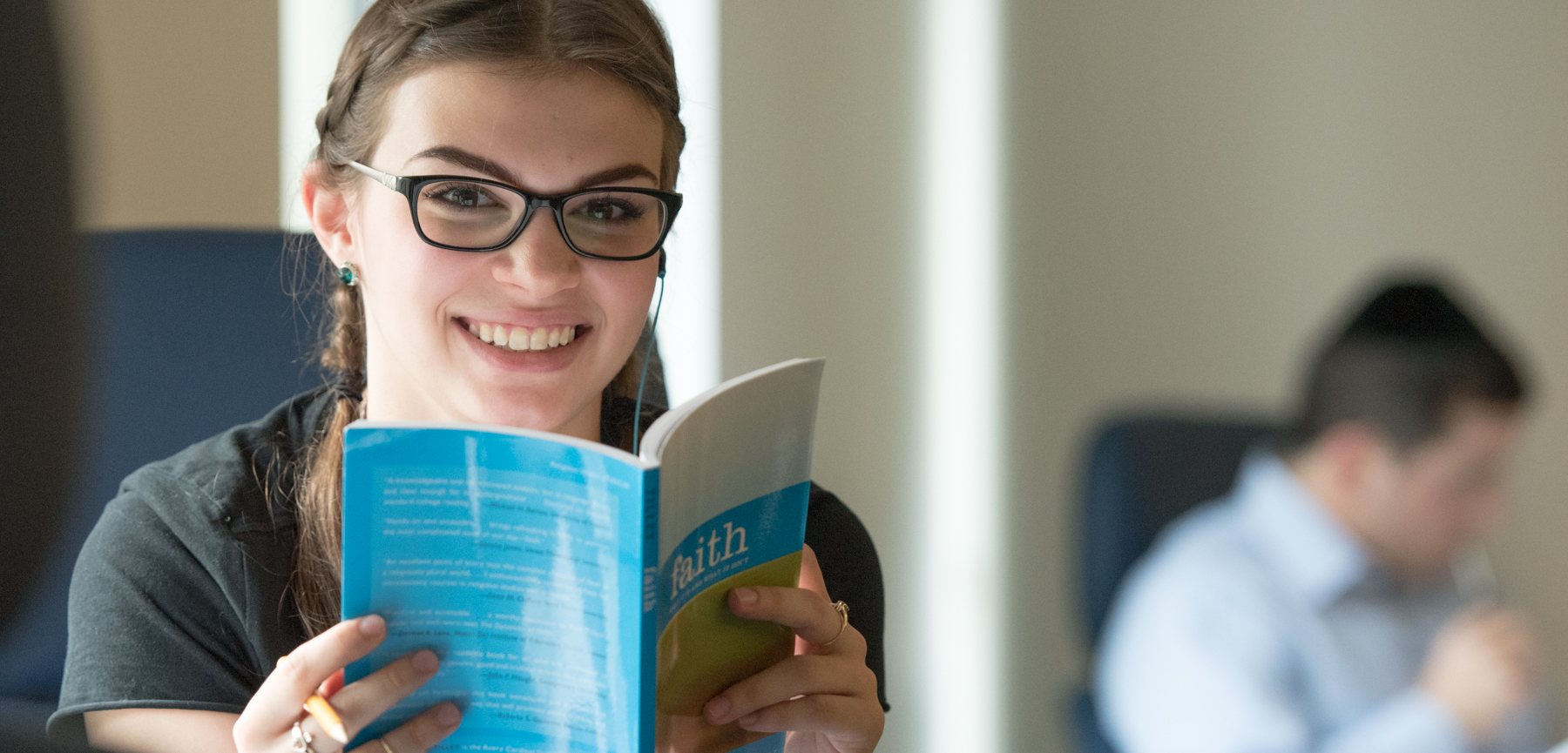 Female Student Peers over Text Book