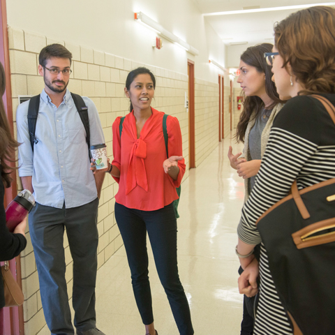 Mixed Group of Students Chatting in Hallway