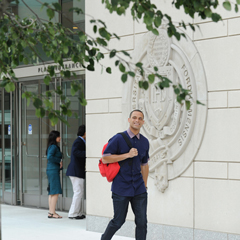 Fordham Law student walking in front of Law School building