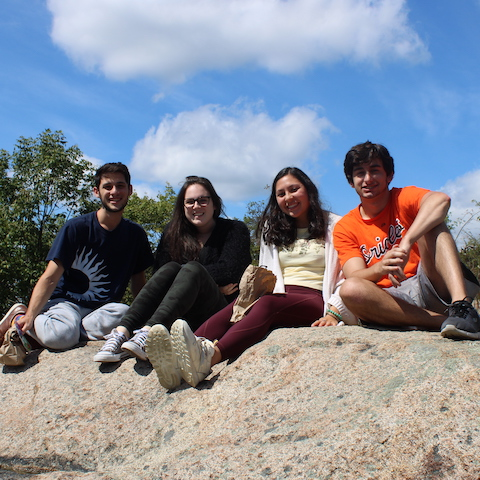 4 students sitting outside on a rock