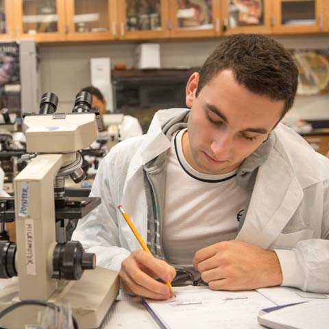 Male student in lab coat writing notes - LG