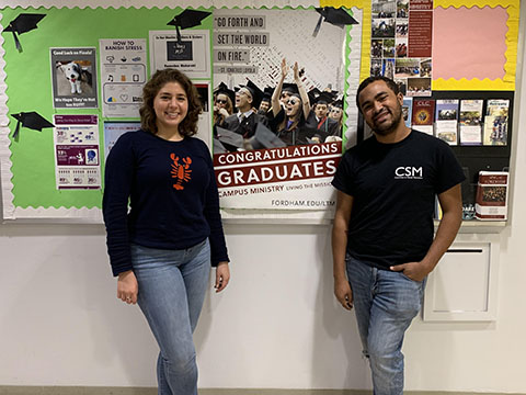 Students in front of a poster congratulating seniors for graduation