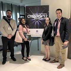 Four students around a sign for the 2018 NYC Cyber 9/12 Challenge
