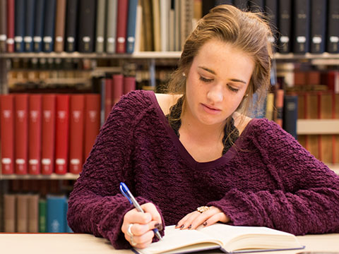 Female Student Writing in Library