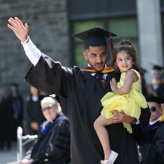 Graduated student holding child and waving.