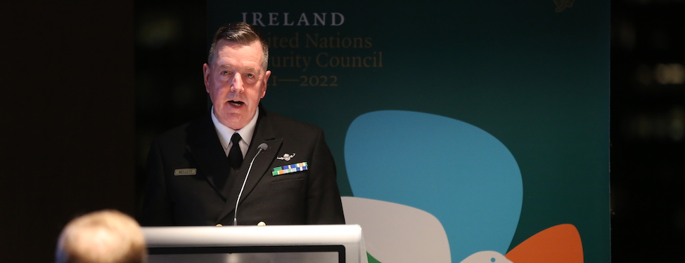 Vice Admiral Mark Mellett speaking at the podium in front of the Permanent Mission of Ireland to the United Nations Banner