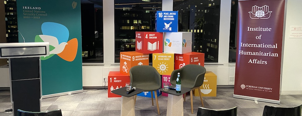 Room setup of chairs with a podium, two banners, and two sets of chairs in front of a display of the United Nations Sustainable Development Goals