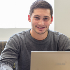 Male student smiling over laptop - SM