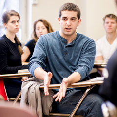 Male Student Emphasizing a Point in Class