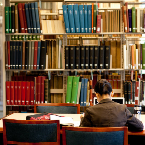 back of female student studying in library