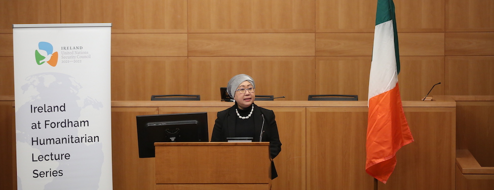 Speaker, Dr. Jemilah Mahmood, stands at the podium in the law school moot courtroom delivering her speech for the Ireland at Fordham Humanitarian Lecture Series