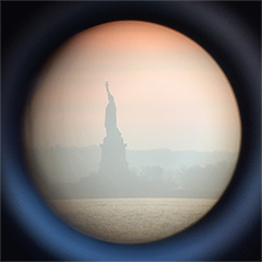 Image is of the Statute of Liberty through a sightseeing telescope near New York City's Pier 40.