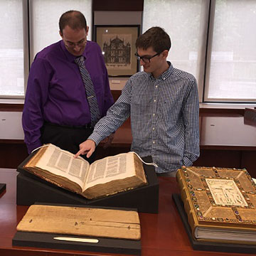 Michael Sanders (Ph.D., History) and David Howes (MA, Medieval Studies; Archives Assistant) present a 15th-century illuminated incunabulum of Justinian's code, and other materials from the University's Special Collections.