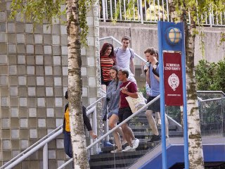 Students walking down the stairs at the main entrance.