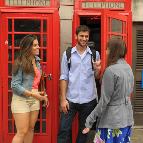Three students in front of British phone booth - LG