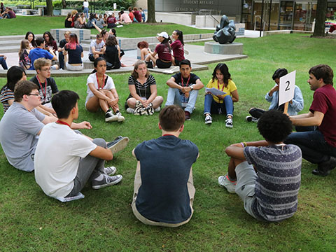 A group of students sitting in a circle outside during orientation