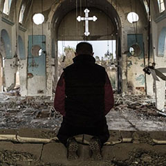 Syrian Christian Kneeling in Damaged Church