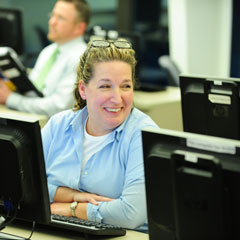 Adult female PCS student smiling at neighbor in computer lab