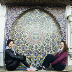 Two Female Students seated in Front of Moroccan Mosaic
