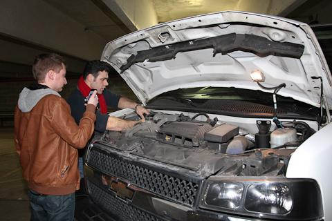 Two students look underneath the hood of a Ram Van