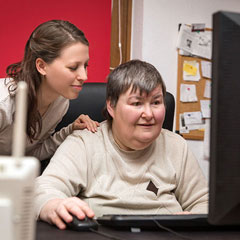 Woman helping older woman on computer