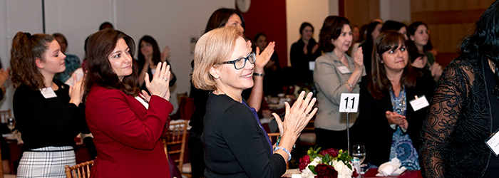 Women clapping and standing at the women's philanthropy summit