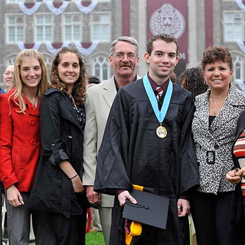 Male grad posing with family - LG