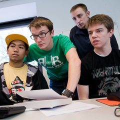 Four Students Focus on a Computer Screen