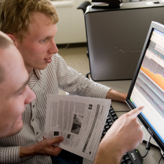 Two Students Looking at Screen with Financial Data